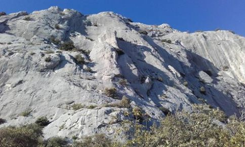 La falaise de Saint Ser - l'Ermitage. La ligne du Mathou est située entre ombre et soleil, dans une rampe évidente ascendante à gauche